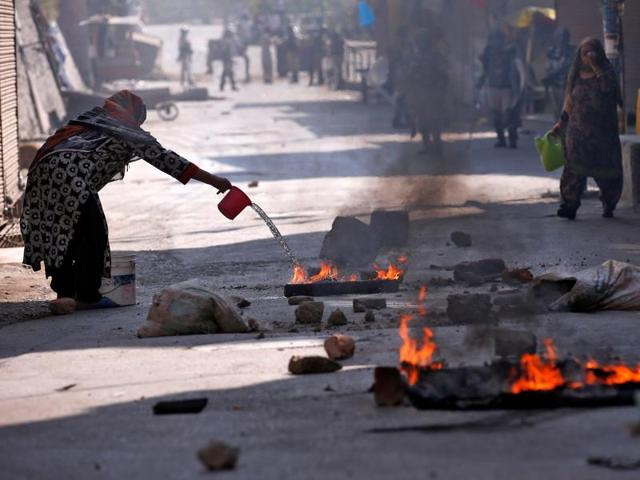 A Kashmiri woman pours water on burning debris after a protest in Srinagar.