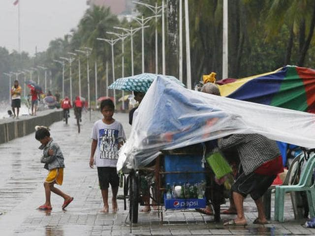 A few residents walk on a promenade under the rain brought about by Typhoon Sarika in Manila, Philippines.