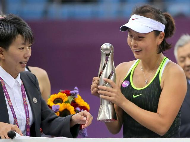 Peng Shuai of China looks at her trophy after winning the singles final match against Alison Riske.
