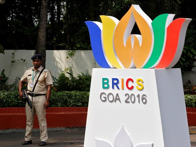 A man rides past a billboard, which shows the faces of all five BRICS  leaders, near one of the venues of the summit in Goa.