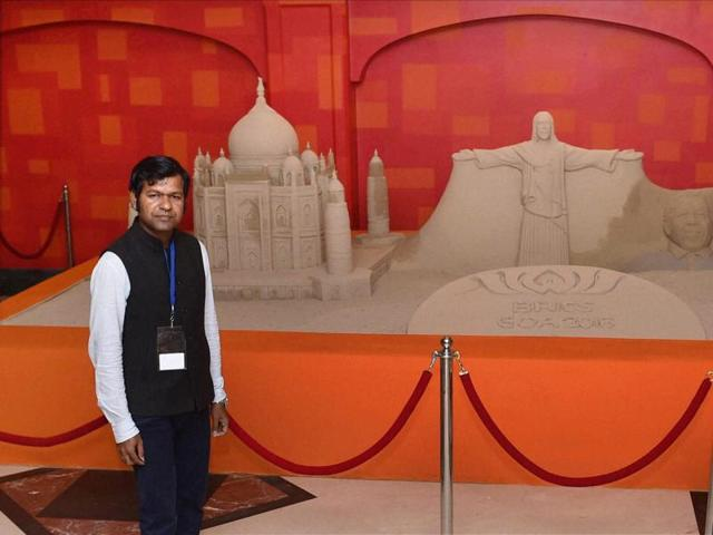 Sand sculpture artist Sudarsan Pattnaik poses with his creation ahead of the 17th India-Russia annual summit in Benaulim, Goa on Saturday.