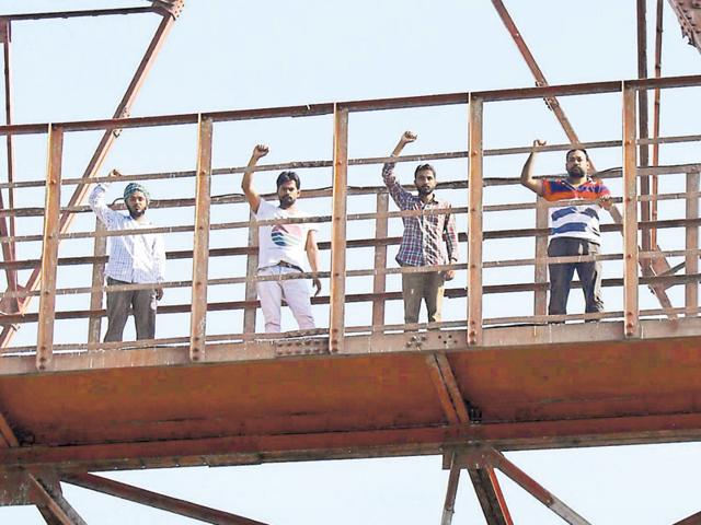 Unemployed teachers protesting atop a TV tower in Bathinda on Sunday.