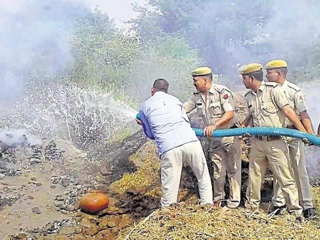 Police officials extinguish the pyre to recover Sugadh Jatav's body in Bharatpur.