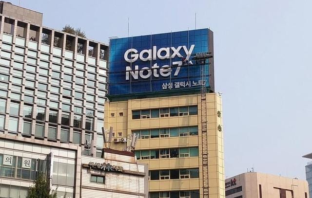 Workers take a billboard of Samsung Electronics' Galaxy Note 7 off from atop a building in central Seoul, South Korea.