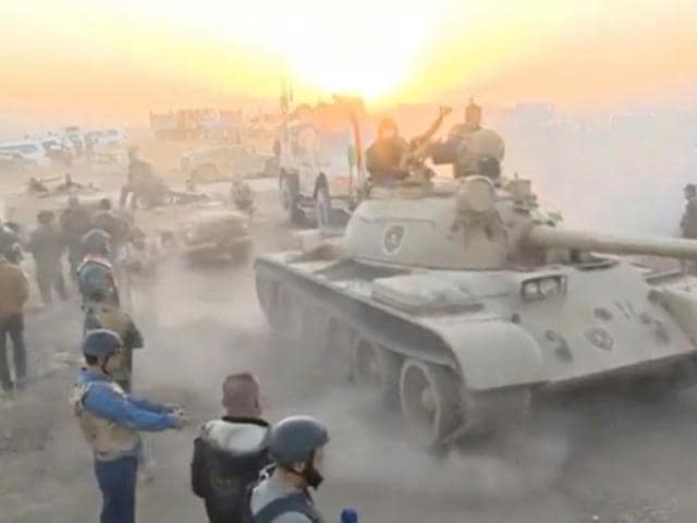 Tanks move past soldiers in military fatigues as the sun begins to set east of Mosul, where the Iraqi government launched a US-backed offensive to drive Islamic State from the northern city.