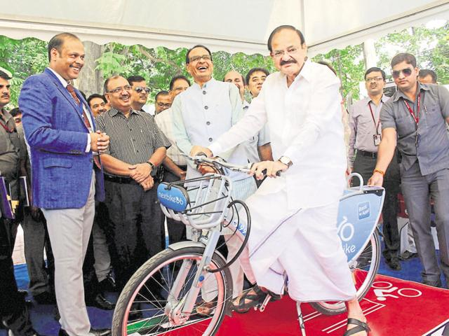 Naidu poses on a cycle in Bhopal on Monday, as chief minister Chouhan looks on.