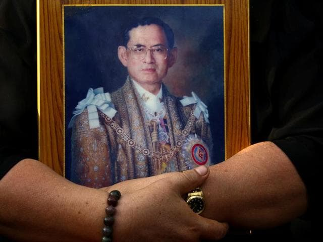 A mourner holds a portrait of Thailand's late King Bhumibol Adulyadej in Bangkok, Thailand.