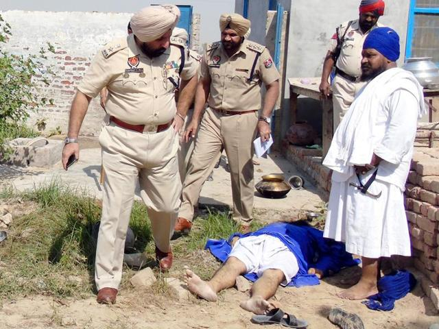 Police and others near the body of one of the victims of the group clash at a gurdwara in Mallan in Muktsar on Wednesday.