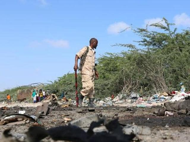 Somali soldiers inspect the scene of a suicide car bomb attack by al Shabaab in Somalia's capital Mogadishu, on Tuesday.