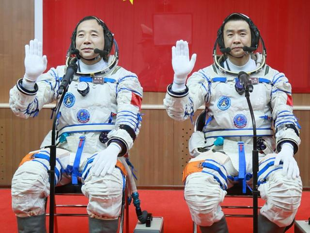 Chinese astronauts Jing Haipeng (left) and Chen Dong salute in the space lab Tiangong 2 on October 19, 2016 . China says a pair of astronauts aboard have entered the country's orbiting space station for a month-long stay.