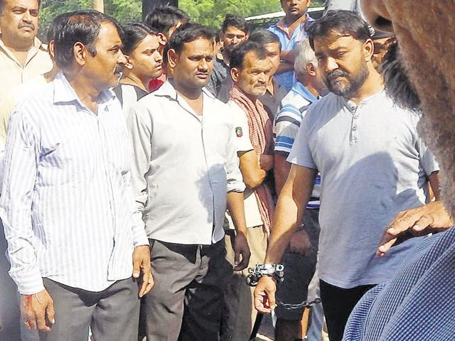Binder Gujjar (in handcuffs), elder to Manoj and younger to Manish, is serving a jail term after being arrested in November for the murder of a rival gang member.
