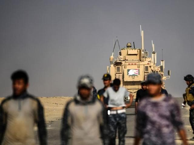 Members of the Iraqi forces walk near an armoured vehicle used by US forces supporting Iraq troops during the operation to recapture Mosul from the Islamic State group, at the Qayyarah military base.