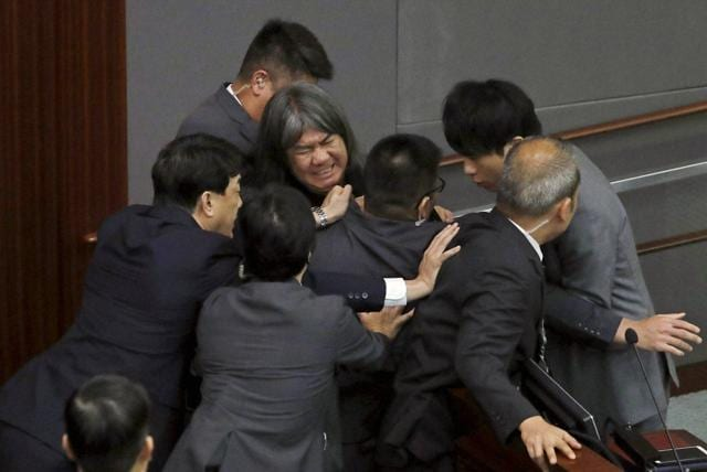 Newly elected pro-democracy lawmaker Raymond Chan Chi-chuen tries to break through the security guards during the election of president of the Legislative Council in Hong Kong on Wednesday.
