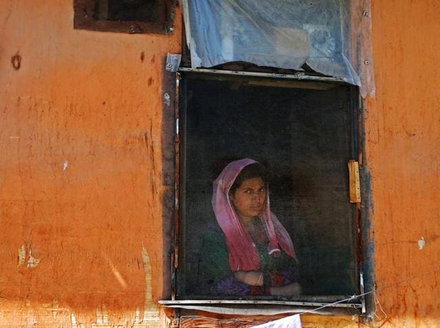 A woman looks out from a window during a protest in Kashmir, Srinagar.