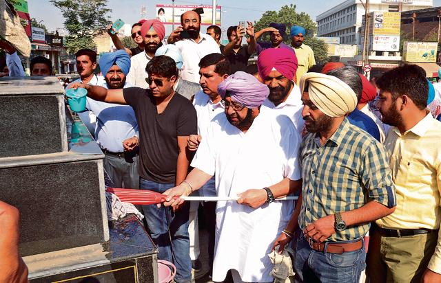 Punjab Congress  president Captain Amarinder Singh cleaning Martyr Nand Singh statue at Bathinda on Wednesday.