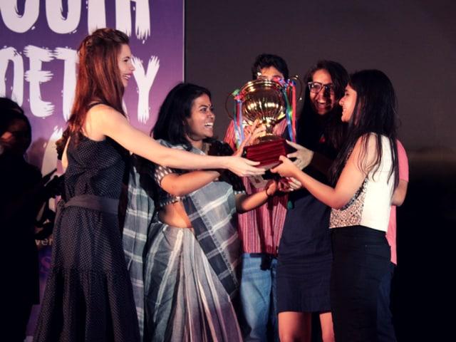 Actor Kalki Koechlin presents an award to Diksha Bijlani, Shubhra Awasthy, and Cheryl Mukherji, students of Gargi College, at the National Youth Slam Poetry.