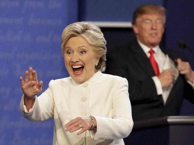Hillary Clinton waves to the audience as Donald Trump puts his notes away after the third presidential debate at UNLV in Las Vegas.