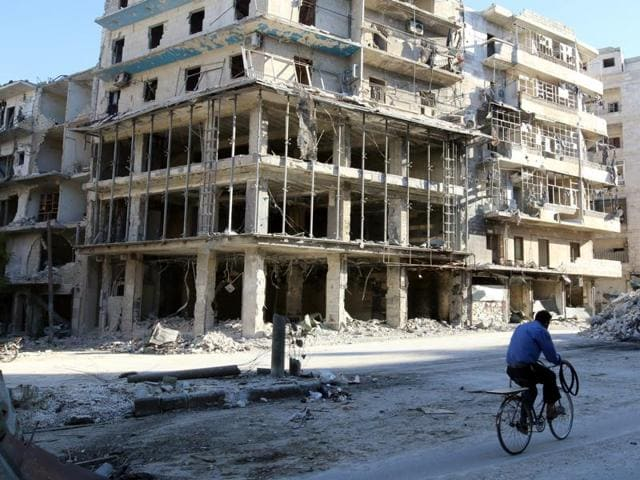 A man rides a bicycle near damaged buildings in the rebel held besieged al-Sukkari neighbourhood of Aleppo. The Syrian army has said it is opening eight corridors to provide safe passage for the more than 250,000 civilians trapped in rebel areas to leave the city.