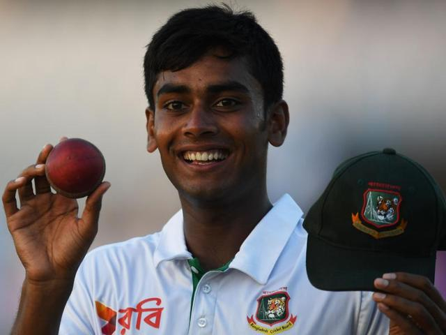 Bangladesh's Mehedi Hasan Miraz shows the ball and test cap for taking five wickets.