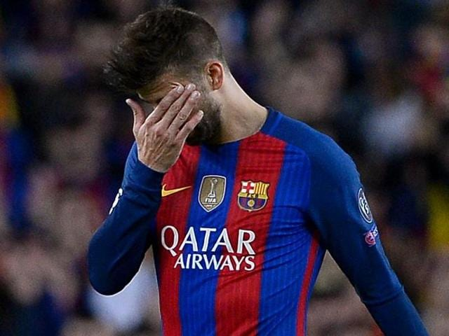 Barcelona's defender Gerard Pique gestures as he leaves the pitch after picking up an injury.