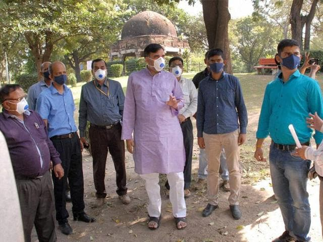 Delhi development minister Gopal Rai covers his face with a mask during a visit to the Delhi zoo.