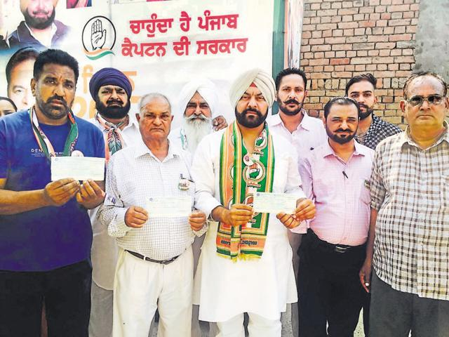 Farmers showing unsigned cheques issued to them for crop damage at Bir Bansian village in Jalandhar on Wednesday.