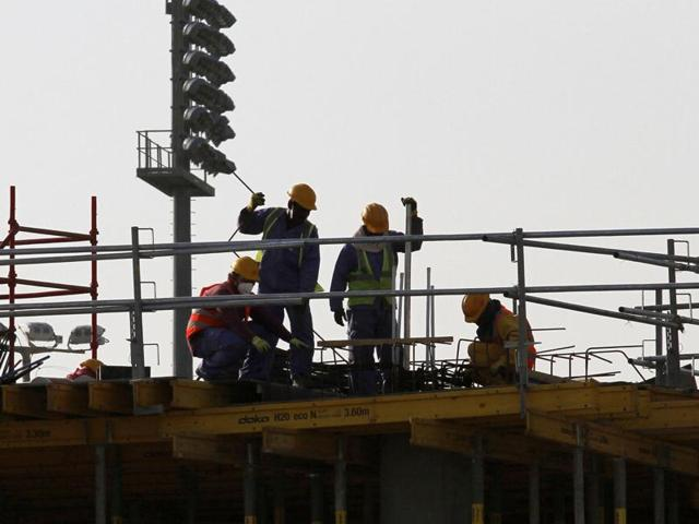Migrant labourers work at a construction site in Doha