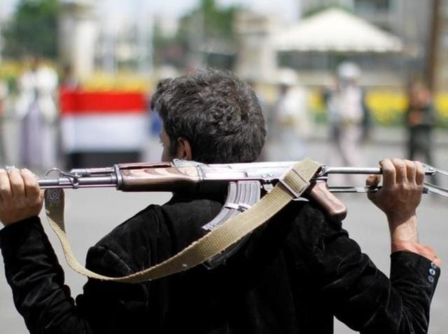 An armed man loyal to the Houthi movement holds his weapon as he gathers to protest against the Saudi-backed exiled government, in the capital Sanaa.
