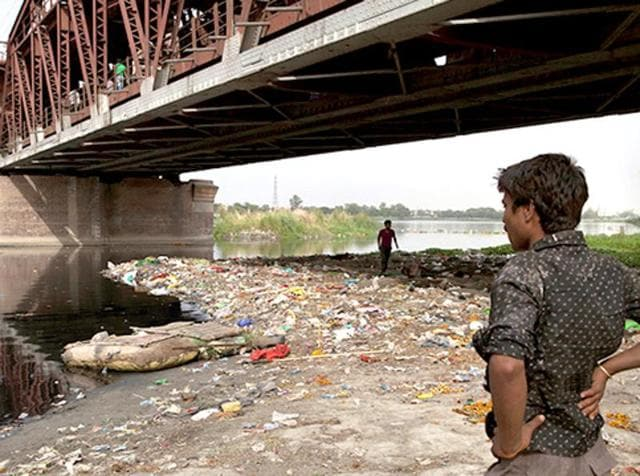 A homeless man stands on the polluted banks of the River Yamuna in New Delhi