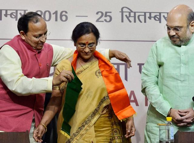 BJP president Amit Shah looks on as party leader Arun Singh presents a scarf to former UP Congress chief Rita Bahuguna Joshi, who joined the BJP in New Delhi on Thursday.