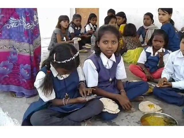 Children are forced to share plates to eat their midday meals at Rozra Chakkar government primary school.