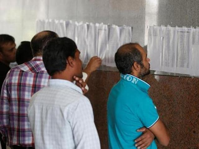 Migrant workers look for their names as they ask for a final settlement over salaries issue, in Riyadh, Saudi Arabia.