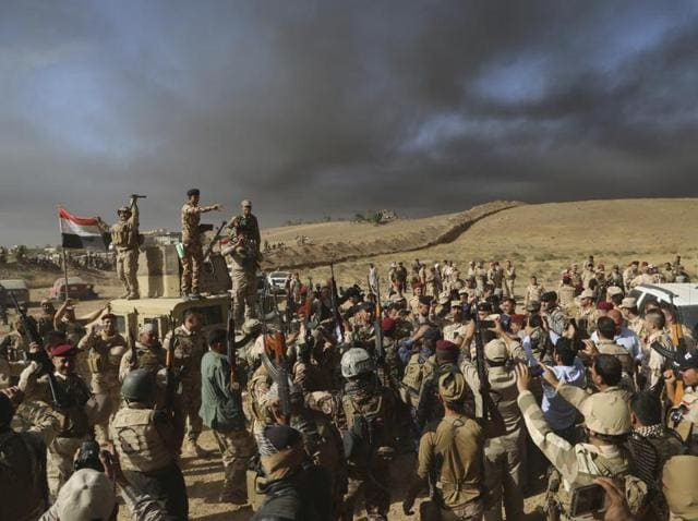 Iraqi army soldiers raise their weapons in celebration on the outskirts of Mosul, Iraq.