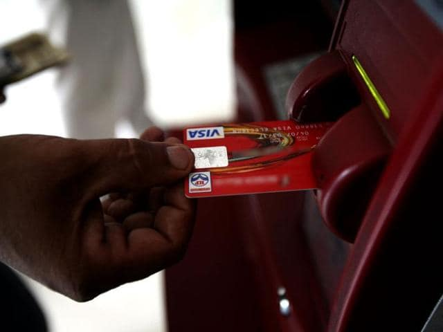 A customer uses his card to withdraw money from an ATM.