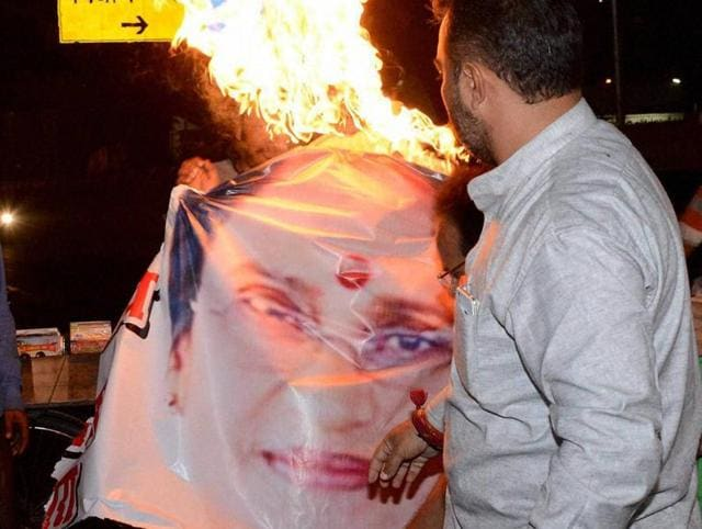Congress workers burn Rita Bahuguna's poster after she left Congress and joined BJP, in Lucknow on Thursday.