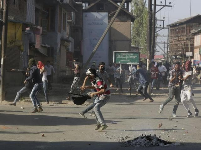 Kashmiri protesters throw stones on police vehicles during a protest in Srinagar, Kashmir.