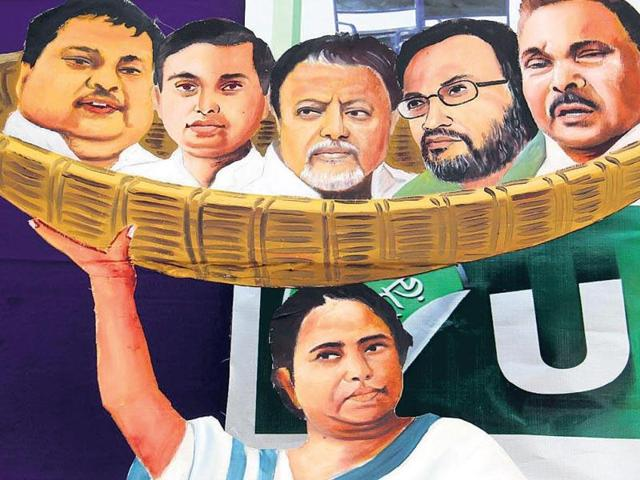 Cartoon showing Mamta Banarjee holding leaders to the Saradha scam in a basket.