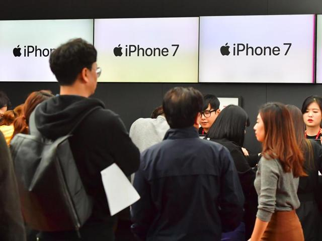 People wait in line to buy new iPhone models at a telecom shop in Seoul.