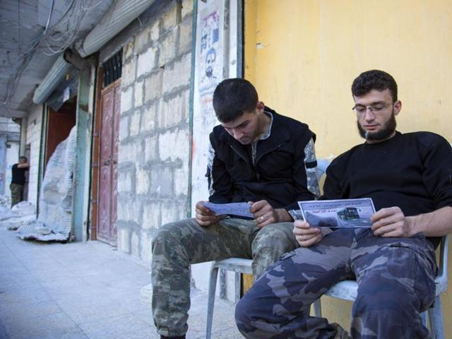 Opposition fighters from the Sham Legion look at flyers reportedly distributed by the government encouraging people to leave a rebel-held area in the northern embattled city of Aleppo on Thursday. A