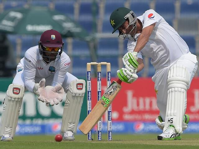 Pakistani batsman Younis Khan (R) plays a shot as West Indies' wicketkeeper Shai Hope looks on during the first day of the second Test between Pakistan and the West Indies.