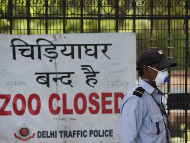 A security guard in front of a banner placed at the main gate of the Delhi zoo that has been temporarily shut down amid bird flu scare.
