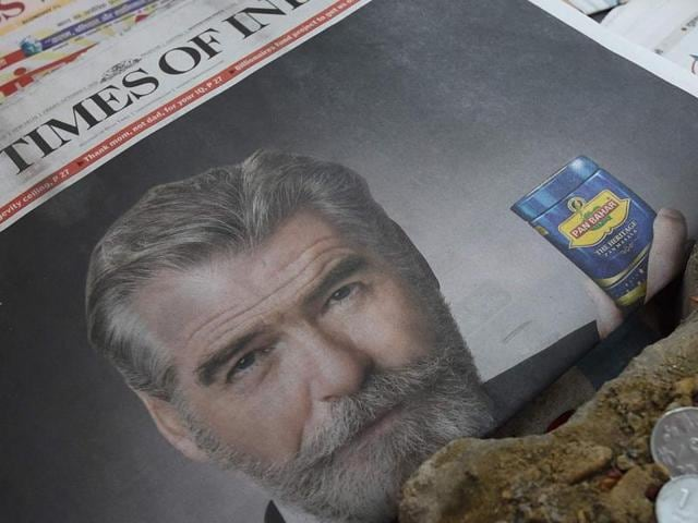 A newspaper with a front page advertisment of former 007 star Pierce Brosnan endorsing a mouth freshener.