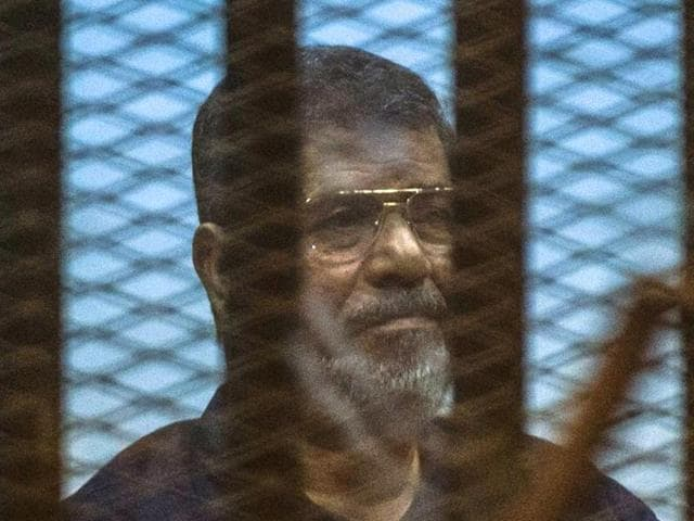 Egypt's deposed Islamist president Mohammed Morsi sits behind the defendant's cage as the judge reads out his verdict in Cairo.