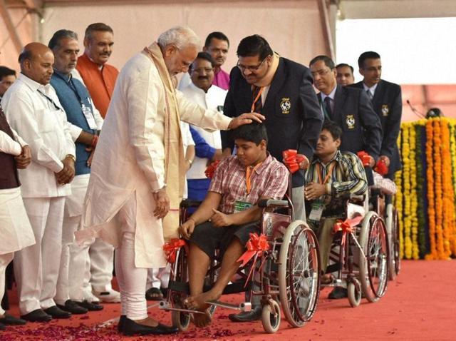 Prime Minister Narendra Modi distributes aid and equipment at the Saamaajik Adhikaarita Shivir in Vadodara.