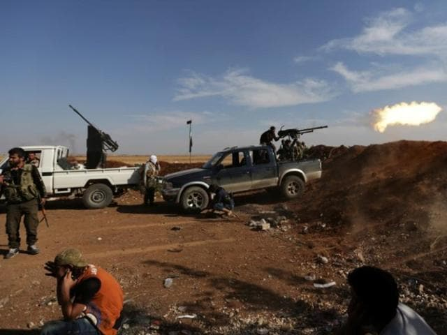 Rebel fighters in Marea city shoot a weapon towards Syria Democratic Forces (SDF) controlled Tell Rifaat town, northern Aleppo province, Syria on October 21.