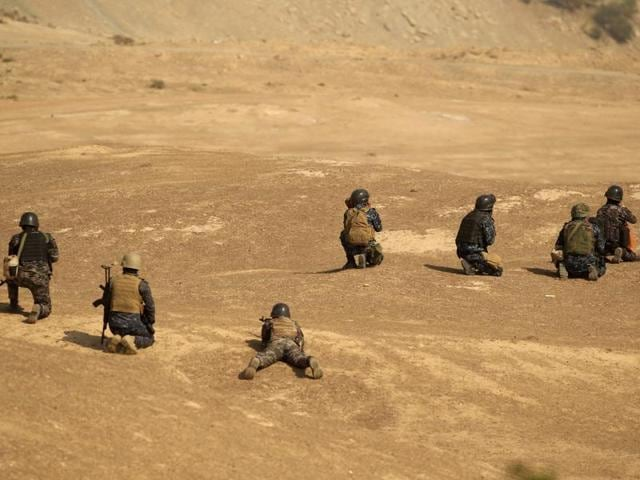 Members of Iraqi forces take position in front of Islamic States positions at the town of Safayah near Mosul, Iraq.