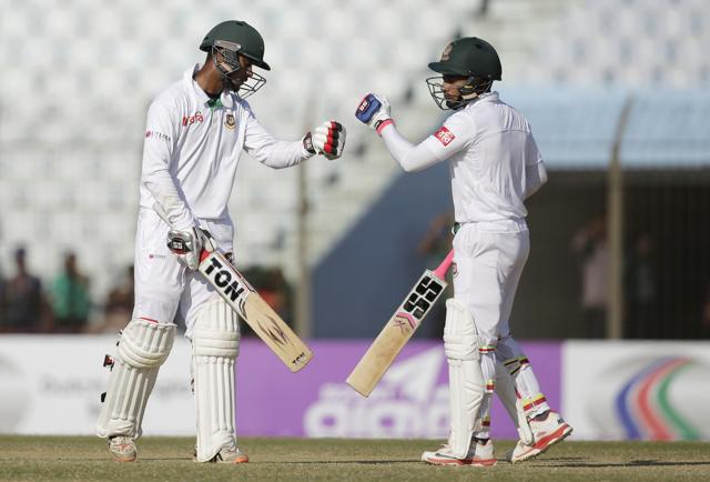 Bangladesh's captain Mushfiqur Rahim, right, and teammate Sabbir Rahman celebrate a boundary shot during the fourth day of their first cricket test match against England in Chittagong, Bangladesh, Sunday, Oct. 23, 2016. (AP Photo/A.M. Ahad)