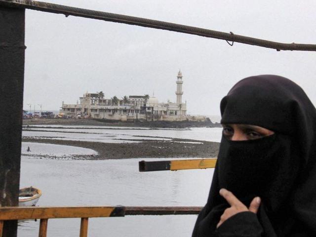 A woman walks outside Haji Ali Dargah in Mumbai.