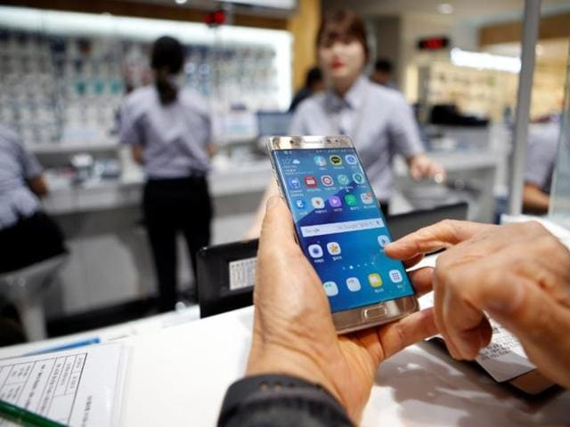 A customer uses his Samsung Electronics' Galaxy Note 7 as he waits for an exchange at company's headquarters in Seoul, South Korea.