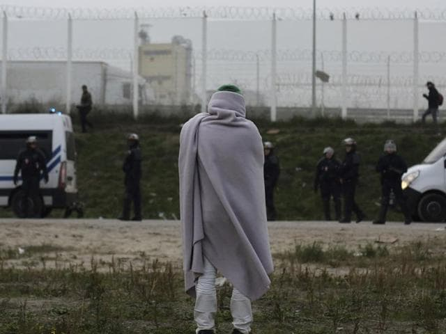 A migrant stands near police trucks in a makeshift migrant camp known as